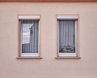 Två fönster på ljus - rosa vägg Fotografering för Bildbyråer