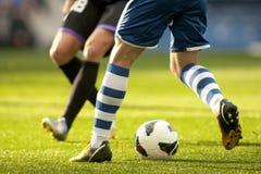 Två fotbollspelare tävlar Royaltyfri Bild