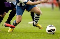 Två fotbollspelare tävlar Arkivfoto
