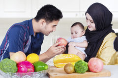 Två föräldrar med den små sonen och frukter Arkivbild