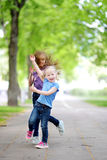 Två förtjusande lilla systrar som skrattar och kramar sig Arkivfoto