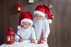 Två förtjusande pojkar som skrivar brevet till jultomten Arkivbilder