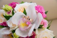 Två gifta sig guld- cirklar med en diamant som ligger på bride&en x27; s-buketten av vita orkidér och rosa färger blommar Royaltyfri Foto