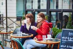 Två gladlynta flickor i ett parisiskt gatakafé Royaltyfria Bilder