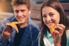 Två gladlynta tonåringar, flicka och pojke som äter utomhus- pizza Royaltyfri Foto