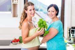Två gravida bästa vän som förbereder sund mat Arkivfoton