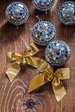 Två guld- pilbågar och juldiskospegel klumpa ihop sig på gammalt träb Arkivfoton