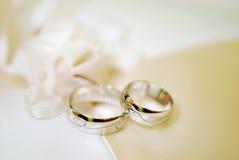 Två guld- vigselringar på vit snör åt blocket Royaltyfri Fotografi