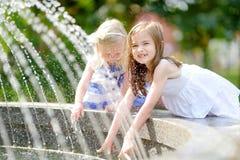 Två gulliga små flickor som spelar med en stadsspringbrunn på varm sommardag Royaltyfri Foto