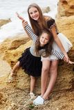 Två gulliga systrar står på stranden Arkivbild