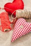 Två hemlagade sydde röda bomullsförälskelsehjärtor. Royaltyfria Foton