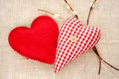 Två hemlagade sydde röda bomullsförälskelsehjärtor med vårpiltwi Royaltyfria Bilder