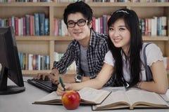 Två högskolestudenter som tillsammans studerar Fotografering för Bildbyråer
