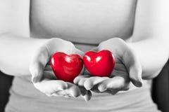 Två hjärtor i kvinnahänder Förälskelse omsorg, hälsa, skydd Royaltyfria Bilder