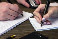 Två händer gör anmärkningar i pennor för en anteckningsboksvart Royaltyfri Bild
