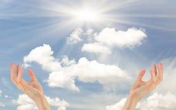 Två händer som ber räckvidden för den molniga himlen Arkivbild