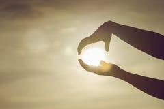 Två händer till att rymma en sol på solnedgångögonblicket som hoppas begrepp, stridighet, tänker stort begrepp Royaltyfria Bilder