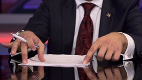 The TV Host Corrects Papers On a Table Before Broadcast stock footage