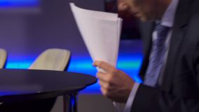 The TV Host Corrects Papers On a Table Before Broadcast. Shot with Sony A7s and Canon lens stock footage