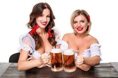 Två härliga blonda och brunettflickor av den mest oktoberfest ölölkruset Fotografering för Bildbyråer