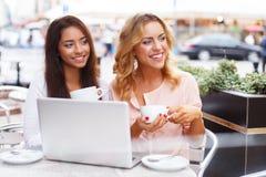 Två härliga flickor i kafé med bärbara datorn Arkivbild