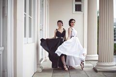 Två härliga flickor i svartvita långa klänningar Royaltyfri Foto