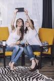 Två härliga kvinnavänner som hemma talar lyckliga leenden Royaltyfria Bilder