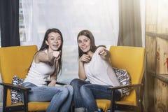 Två härliga kvinnavänner som hemma talar lyckliga leenden Royaltyfri Bild