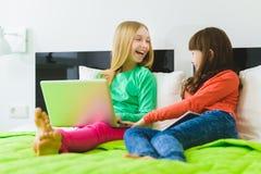 Två härliga lilla systrar som sitter på säng och lek med en minnestavla eller en bärbar dator Arkivbild