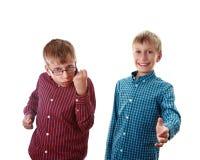 Två härliga pojkar i färgrika skjortor som visar gester av agression och välkomnandet Royaltyfria Bilder