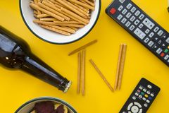 TV inscription, beer and remote controls. Weekend, leisure and hobby concept. A TV inscription made of bread sticks in a frame of beer bottle, snacks and remote Royalty Free Stock Photography