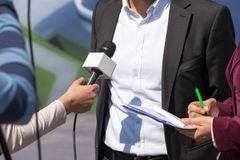 TV interview. News conference. Journalist. Press conference. Media interview. Microphone Stock Photo