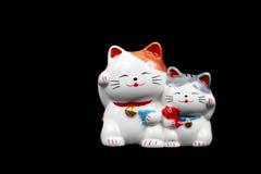 två keramiska lyckliga katter för garnering som isoleras på svart Royaltyfri Fotografi