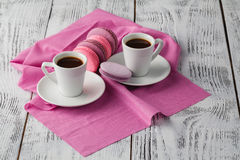 Två kopp av espressokaffe med makron på rosa bakgrund Royaltyfri Fotografi
