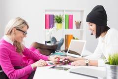 Två kopplade av idérika unga kvinnor som använder minnestavladatoren i kontoret Arkivbilder