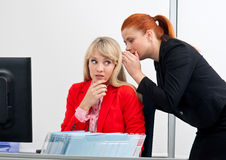 Två kvinnacolegues skvallrar i regeringsställning Arkivfoto