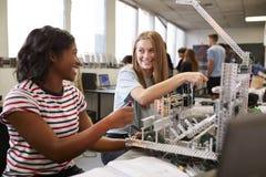 Tv? kvinnliga h?gskolestudenter som bygger maskinen i vetenskapsrobotteknik eller iscens?tter grupp royaltyfri fotografi