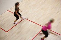 Två kvinnliga squashspelare i snabb handling på en squashdomstol Royaltyfri Bild