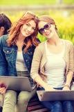 Två kvinnliga studenter med bärbar datordatorer Fotografering för Bildbyråer