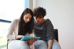 Två kvinnliga studenter som ser minnestavlaPC Royaltyfria Bilder
