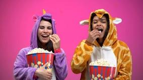 Tv? kvinnor i enh?rning- och giraffpyjamas som ?ter popcorn och h?ller ?gonen p? komedi arkivfoto