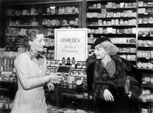 Två kvinnor i ett apotek som ser de (alla visade personer inte är längre uppehälle, och inget gods finns Leverantörwarran Royaltyfria Bilder