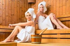 Två kvinnor i wellnessbrunnsort som tycker om bastuavkoken Royaltyfria Bilder
