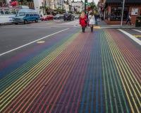 Två kvinnor korsar Castro Street med dess regnbågefärger Royaltyfri Fotografi