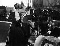 Två kvinnor med bilen (alla visade personer inte är längre uppehälle, och inget gods finns Leverantörgarantier att det inte ska f Arkivbilder