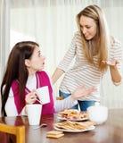 Två kvinnor som har konflikt över te Arkivfoton