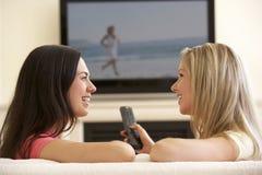Två kvinnor som hemma håller ögonen på ledsen film på Widescreen TV Royaltyfri Fotografi