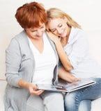 Två kvinnor som ser fotoboken Royaltyfri Fotografi