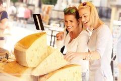 Två kvinnor som shoppar för ost på matmarknad Royaltyfri Foto