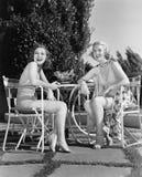 Två kvinnor som tillsammans sitter i en bakgård (alla visade personer inte är längre uppehälle, och inget gods finns Leverantörga Royaltyfria Bilder